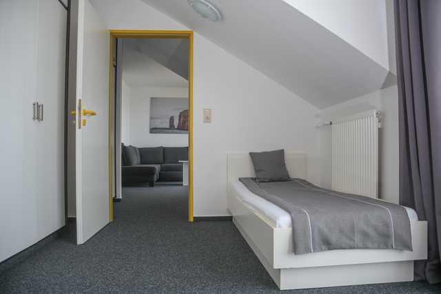 Einzelbett i Schlafzimmer mit Blick auf das Wohnzimmer